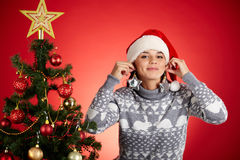 Christmas earrings. Attractive girl in Santa cap trying on decorative toy stars with xmas firtree near by stock images