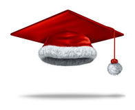 Christmas Education Holiday. Concept with a mortar board or graduation cap as a red velvet santa clause hat with white fur trim as a festive symbol of winter Royalty Free Stock Images