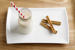 Christmas Egg Nog with cinamon on white plate. Christmas Egg Nog in a mini milk pot with cinnamon on a white plate Stock Image