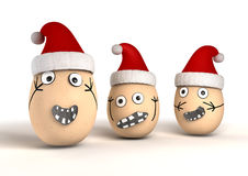 Christmas Eggs. 3 made up egg characters with stuck on features and human emotion that are wearing red christmas hats Stock Photos