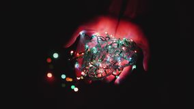 Christmas electric garlands, festive attribute, shimmer different colors in the palms of the girl.