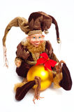 Christmas elf. Doll wearing beautiful brown pursuit and holding yellow sphere ball with red bow in his hands. Against white background Stock Photos