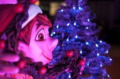 Christmas Elf. Christmas decorations featuring an elf a blue lighted Christmas tree Stock Photo