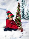 Christmas elf. A christmas elf sitting in the snow, putting a present under the christmas tree Royalty Free Stock Photography