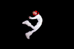 Christmas elf acrobat. Guy gymnast dressed as christmas elf flying without visible ropes isolated on black background Royalty Free Stock Photography