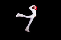 Christmas elf acrobat. Guy gymnast dressed as christmas elf flying without visible ropes isolated on black background Royalty Free Stock Photo