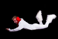 Christmas elf acrobat. Guy gymnast dressed as christmas elf flying without visible ropes isolated on black background Royalty Free Stock Images