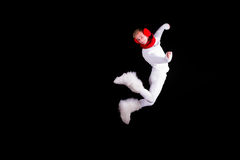 Christmas elf acrobat. Guy gymnast dressed as christmas elf flying without visible ropes isolated on black background Stock Photo