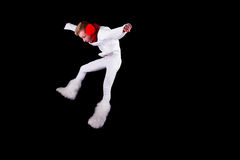 Christmas elf acrobat. Guy gymnast dressed as christmas elf jumping in the air isolated on black background Stock Photo