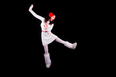 Christmas elf acrobat. Young woman gymnast dressed as christmas elf  dancing isolated on black background Royalty Free Stock Photography