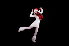 Christmas elf acrobat. Young woman gymnast dressed as christmas elf dancing isolated on black background Stock Photo