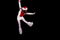 Christmas elf acrobat. Young woman gymnast dressed as christmas elf jumping in the air without visible ropes isolated on black background Stock Image