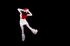 Christmas elf acrobat. Young woman gymnast dressed as christmas elf jumping in the air without visible ropes and looking down isolated on black background Stock Photos