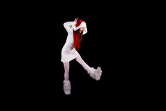 Christmas elf acrobat. Young woman gymnast dressed as christmas elf jumping in the air without visible ropes and looking down isolated on black background Royalty Free Stock Photo
