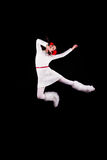 Christmas elf acrobat. Young woman gymnast dressed as christmas elf posing in the air without visible ropes isolated on black background Stock Images