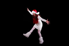 Christmas elf acrobat. Young woman gymnast dressed as christmas elf is posing as if she is going to fall isolated on black background Royalty Free Stock Photos