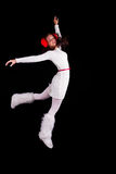 Christmas elf acrobat. Young woman gymnast dressed as santa`s elf jumping in the air without visible ropes isolated on black background Royalty Free Stock Photos