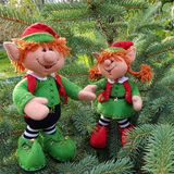 Christmas elf felt decoration on a spruce branch. Handmade bauble figurines elves. Holiday background with a copy space