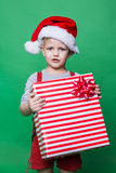 Christmas Elf holding big red gift box with ribbon. Santa Claus helper Stock Images