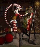 Christmas elf is painting a Santa Claus portrait Royalty Free Stock Photo