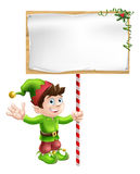 Christmas elf with sign. A Christmas elf or pixie or Santa's helper holding a large Christmas sign in traditional elf clothes Royalty Free Stock Images