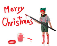 Christmas Elf Sign Painter. A young girl dressed as Sant's Elf, painting a red Merry Christmas sign with an over-sized artist's brush. She's surrounded by paint royalty free stock photography