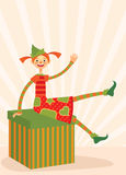 Christmas elf sitting on a gift box Royalty Free Stock Image