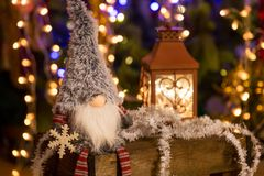 Christmas elf on a wooden bench and Christmas tree. On background stock image
