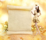 Christmas elf. Young gorgeous woman as  on golden background with blank scroll stock photo