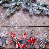 Christmas elfs  and branches fur tree on aged wooden background Royalty Free Stock Images