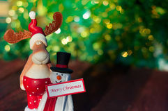 Christmas Elk with a snowman standing on a blurred background Ch Stock Images