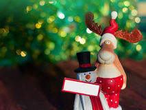 Christmas Elk with a snowman standing on a blurred background Royalty Free Stock Images