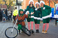 Christmas elves. AYLESBURY, UK - NOVEMBER 30: Performers dressed as Christmas elves parade through Aylesbury market square alongside other acts as part of the Stock Photography