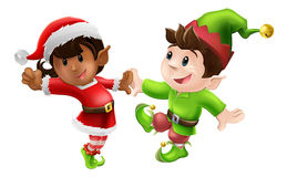 Christmas Elves Dancing. Two happy Christmas elves enjoying a Christmas dance in Santa outfit and elf clothes Royalty Free Stock Photo