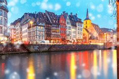 Christmas embankment in Strasbourg, Alsace. Picturesque Christmas quay and church of Saint Nicolas with mirror reflections in the river Ile during evening blue Royalty Free Stock Photos