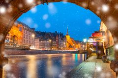 Christmas embankment in Strasbourg, Alsace. Picturesque Christmas quay and church of Saint Nicolas with mirror reflections in the river Ile at snowy christmas Royalty Free Stock Photo