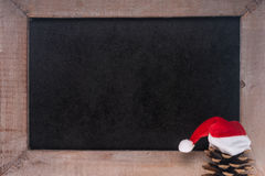 Christmas. Empty blackboard with pine cone and santa claus hat Stock Image
