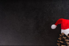Christmas. Empty blackboard with pine cone and santa claus hat Royalty Free Stock Photo