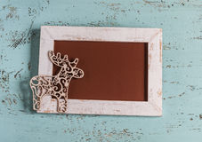 Christmas empty picture frame and decorative Christmas deer. On a blue wooden surface Royalty Free Stock Images