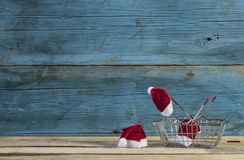 Christmas and empty shopping basket. Santa hats and empty shopping basket on wooden tabletop Royalty Free Stock Images