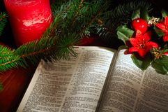 Christmas ensemble. Bible open to the Christmas passage of Luke 2 with evergreen sprigs, candle, and poinsettia decor Royalty Free Stock Images