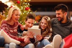 Christmas entertainment at home family watching video on digital. Christmas entertainment at home smiling family watching video on digital tablet Royalty Free Stock Images