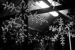 A large Christmas garland in the shape of a beautiful snowflake, decorates the city and shines brightly at night, black and white royalty free stock images