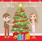 Christmas Eve. A boy and a girl hanging christmas decorations on a christmas tree Royalty Free Stock Photo