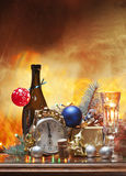 Christmas and the eve. A golden background,a bottle of sparkling wine with a glass of it,an alarm clock signing midnight and then some decorations and lights Royalty Free Stock Image