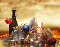 Christmas and the eve. A golden background,a bottle of sparkling wine with a glass of it,an alarm clock signing midnight and then some decorations and lights Stock Photography