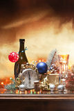Christmas and the eve. A golden background,a bottle of sparkling wine with a glass of it,an alarm clock signing midnight and then some decorations and lights Royalty Free Stock Photography