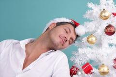 Christmas eve. Man with santa hat on christmastree stock photos