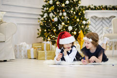 Christmas Eve. Children write letters to Santa Claus. Boy and girl of younger school age lie on a floor near the decorated Christmas tree. Children have Royalty Free Stock Images