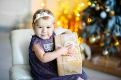 Christmas Eve. cute little girl opening gift box under christmas tree in festive house interior stock images
